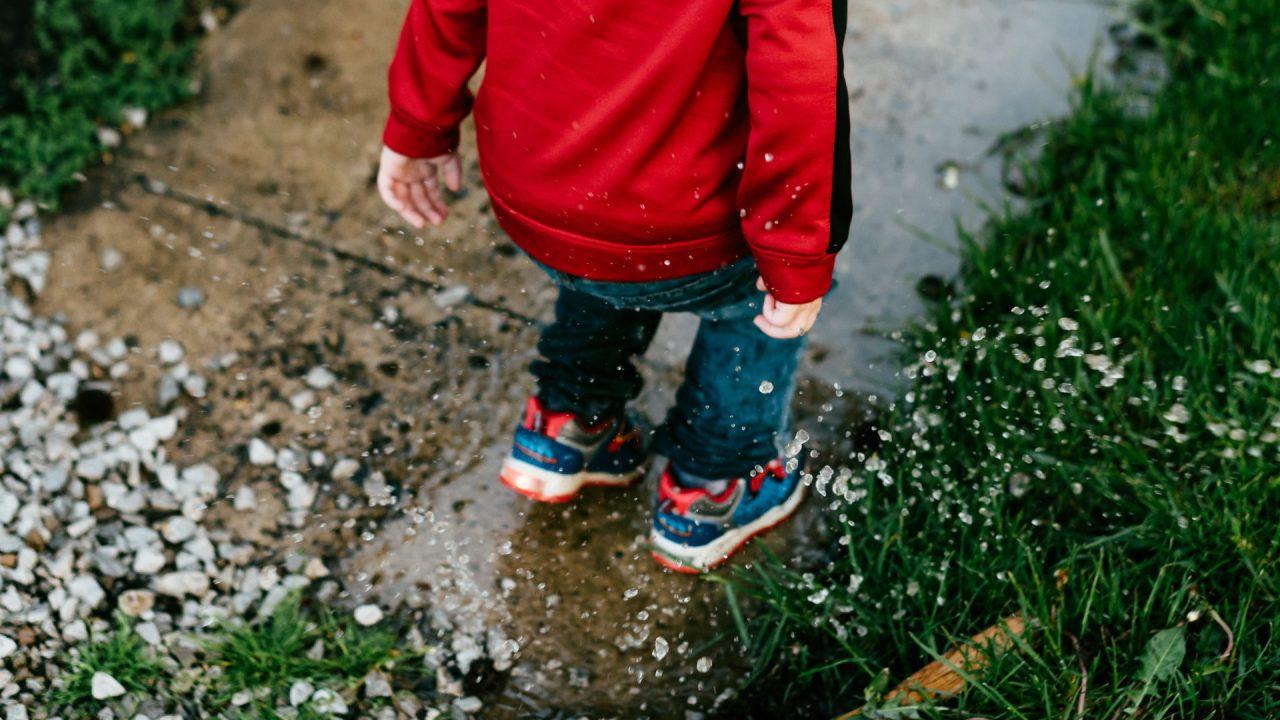 Barn i rød jakke og gummistøvler, stock foto