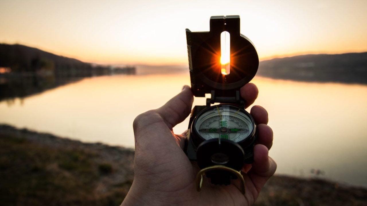 Kompas, hånd, solnedgang