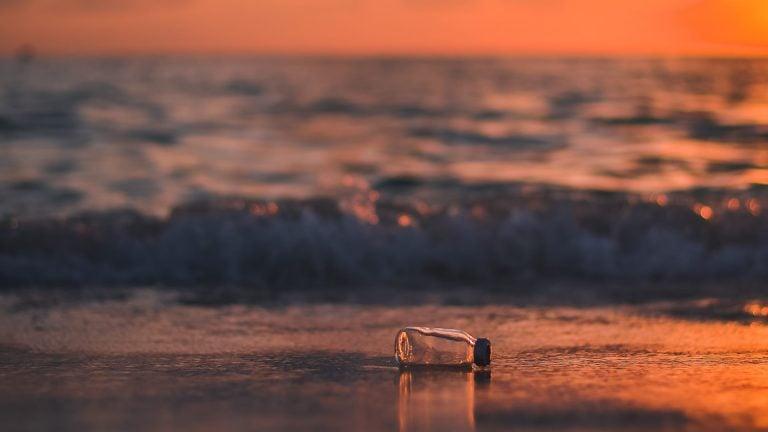 Plastik flaske på strand, stock foto